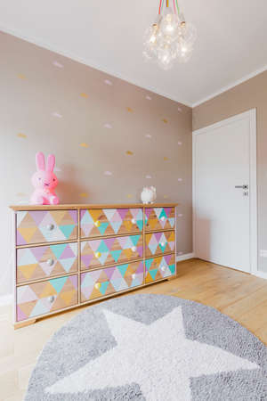 commode: Baby girl room with a colorful commode, deocrative chandelier and star carpet Stock Photo