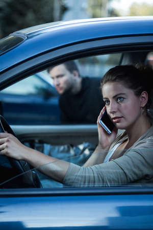 clout: Shot of a young woman driving while talking over a phone and a man sneaking towards the car Stock Photo
