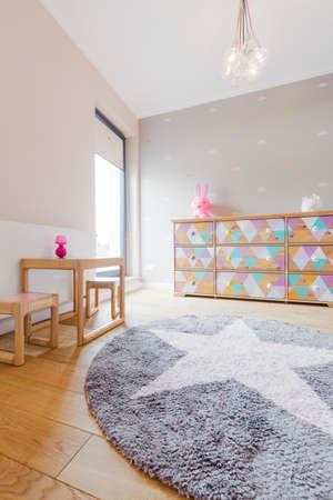 muebles de madera: Spacious child bedroom with a decorative star carpet and simple wooden furniture