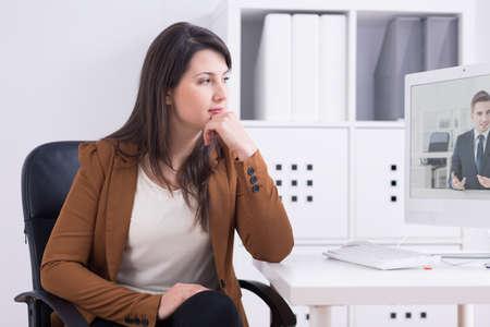 オンライン ビデオ プレゼンテーションに聴いて現代オフィスで若い女性が保有する若いお洒落男