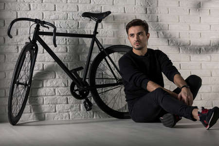 loner: Shot of a young man sitting in front of a black bicycle and a brick wall