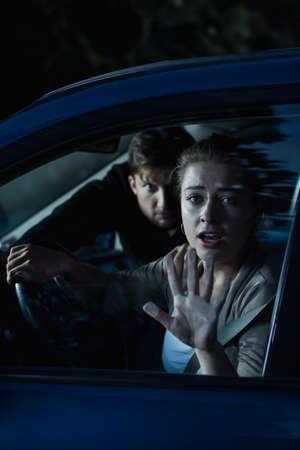 robo de autos: Disparo de un hombre extraño entrar en el coche de una mujer asustada Foto de archivo