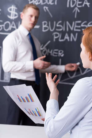 business rival: Co-workers during business presentation, blackboard with a business plan drawn in the background