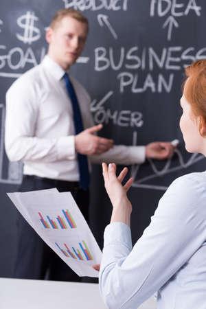 pensamiento estrategico: Compa�eros de trabajo durante la presentaci�n de negocios, la pizarra con un plan de negocios dibujan en el fondo