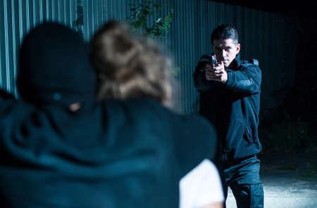 attacker: Young policeman aiming his gun at an attacker at night