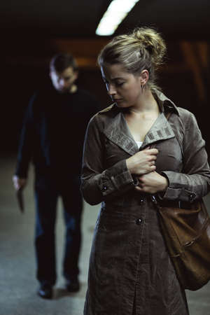 Shot of a man following a young woman on a street at night Stock Photo