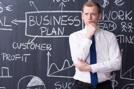pensamiento estrategico: hombre de negocios pensativo que sostiene la barbilla, plan de negocios dibujado en una pizarra en el fondo