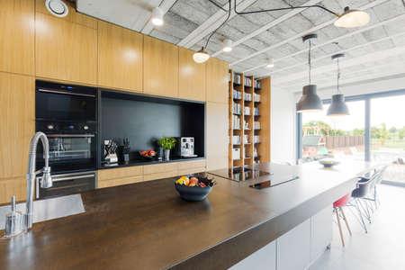 Nuova cucina di design piano aperto con illuminazione decorativa e mobili in legno Archivio Fotografico
