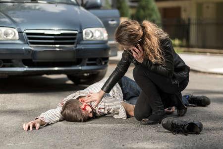 injured woman: Image of woman calling ambulance for injured man