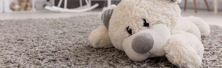 Cerca de un oso de peluche acostado en una alfombra, panorama