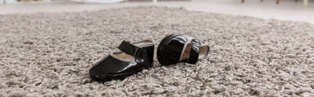 babygirl: Little black baby shoes lying on a carpet, panorama Stock Photo