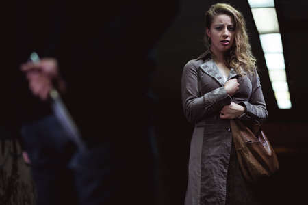 young knife: Shot of a scared young woman looking at a man whos holding a knife behind his back