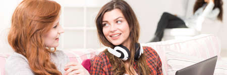 girl with laptop: Two friends sitting on a sofa, brunette girl with headphones holding laptop, panorama Stock Photo