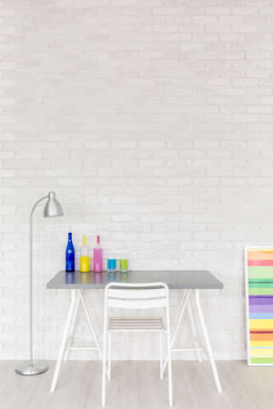 Small desk with chair by the white brick wall in spacious office. On the desk colorful bottles