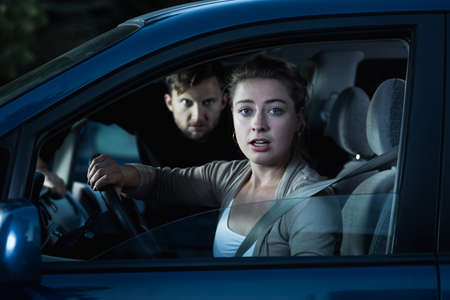 clout: Shot of a scared young woman looking at the camera while a strange man is getting into her car