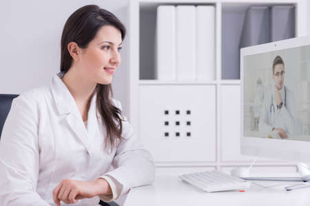 communicator: Shot of a young female doctor in a white doctors room having a video chat with her colleague Stock Photo
