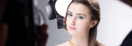 visagiste: Young model during beauty session at professional studio, panorama