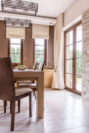 comfort room: Shot of a modern stylish dining room with huge windows