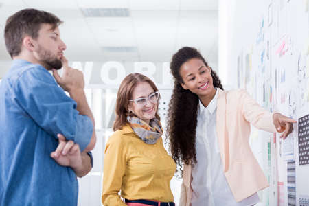 stock photo team of three people of different ages in a very bright modern office space looking at some graphic prints bright modern office space