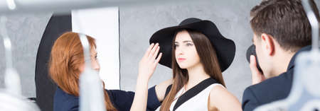 visagiste: Photo model posing with a hat, photographer and stage manager during photo session, panorama Stock Photo