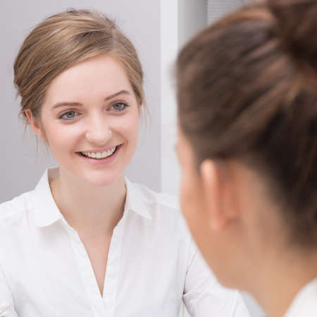 Young beauty businesswoman talking with client - square