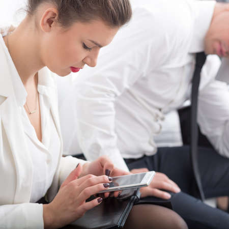 sending: Corporate worker with mobile phone sending text message
