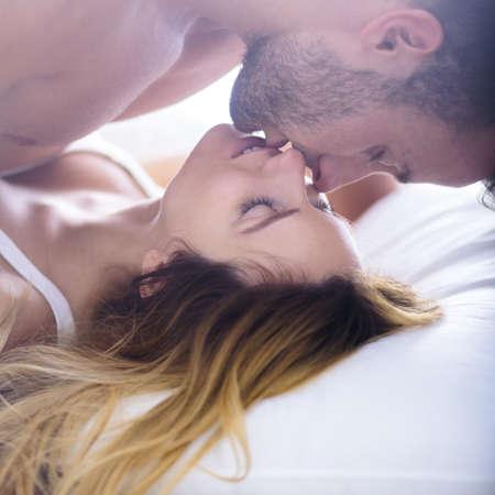 Bild der schönen Frau, die ihren Freund im Bett verführt