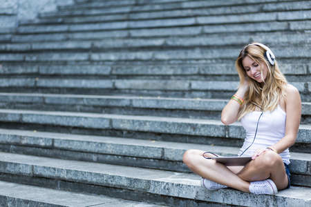 people listening: Shot of a young blonde woman sitting on stairs and listening to music Stock Photo