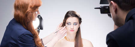 visagiste: Makeup artist, young model and photographer during photo session, panorama