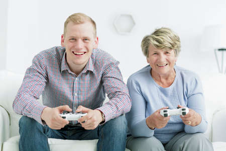 Happy grandmother and grandson playing video games, holding gamepads Stock Photo
