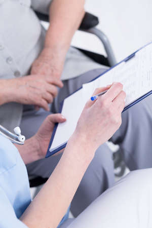 clinic history: Fotograf�a recortada de un m�dico y su paciente mirando el expediente m�dico