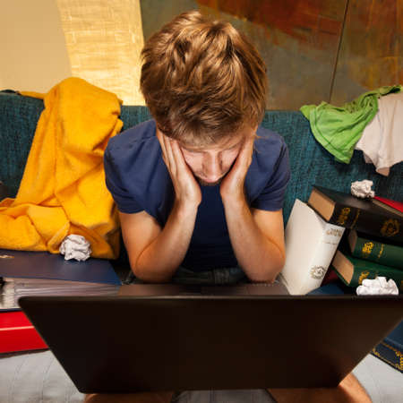 man studying: Top view of exhausted student sitting on the couch with laptop