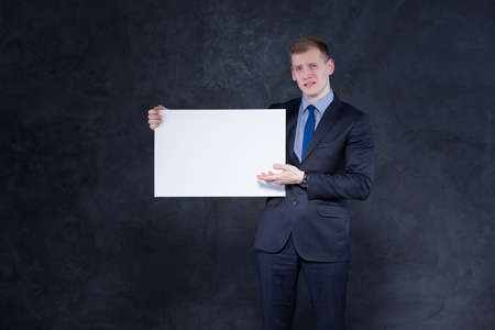 unhappy man: Shot of a very unhappy young man in a suit holding a large sheet of empty paper and pointing at it in a gesture of dissatisfaction