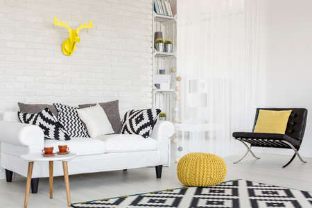 Shot of a black and white living room with yellow accessories