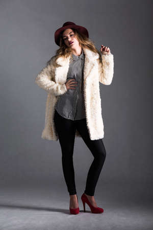animal fur: Young woman is posing with self-assurance