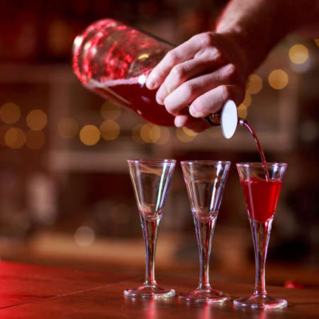 coctail: Close-up of barmans hands pouring red shots Stock Photo