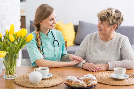 repast: Caregiver and a senior lady sitting at a table, having coffee and cake together, looking affectionately at each other