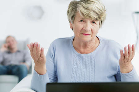 teach: Sad elderly woman sitting in the front of laptop, in the background young man talking on cellphone Stock Photo
