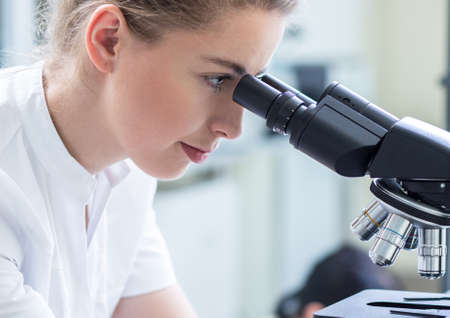 research science: Young woman scientist using a professional microscope Stock Photo