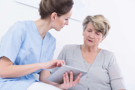 medical professional: Shot of a young doctor holding a tablet and talking to her patient