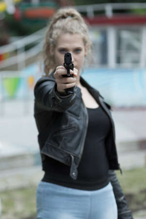 irritation: Young girl in leather jacket with a gun in her hand, pointing straight ahead