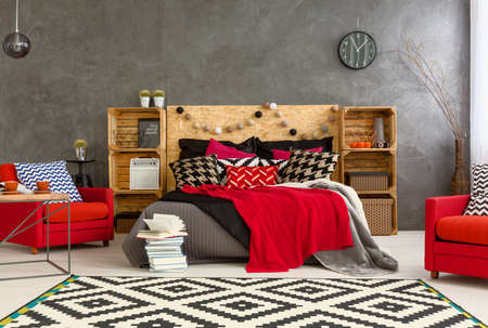 patterns and colors: Spacious bedroom with grey walls and big double bed with decorations. On the both sides of bed two red armchairs and wooden shelves Stock Photo