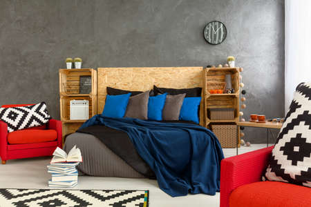 headboard: Stylish bedroom with grey walls and red armchair with little mess on bed. Wooden headboard of the bed and shelves made of wooden boxes