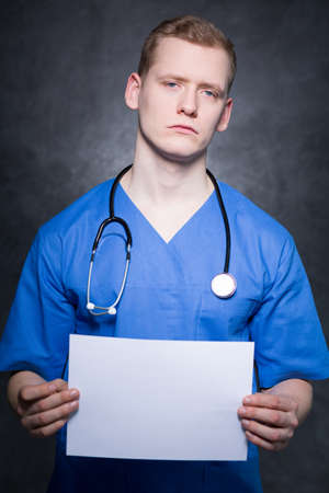 devastated: Portrait of a young red-haired physician with devastated facial expression, holding an empty sheet of paper Stock Photo