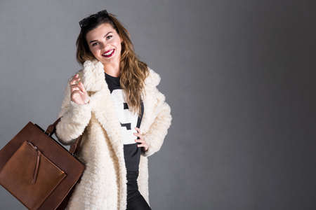 causal clothing: Cheerful woman is posing with bag hung over her shoulder