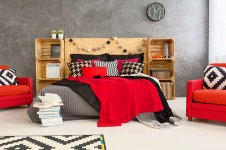 headboard: Grey room with double bed with wooden headboard. Red comfortable armchairs and wooden shelves in spacious bedroom
