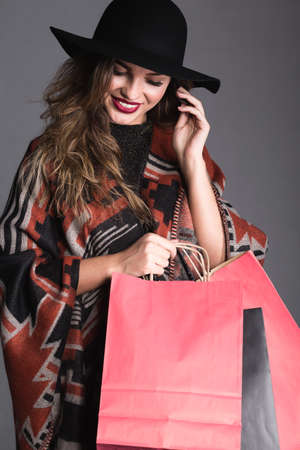 ethnic woman: Woman is gently touching her hair and carrying few shopping bags