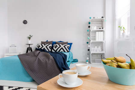 coffees: Stylish bedroom with large bed, two coffees standing on wood table Stock Photo
