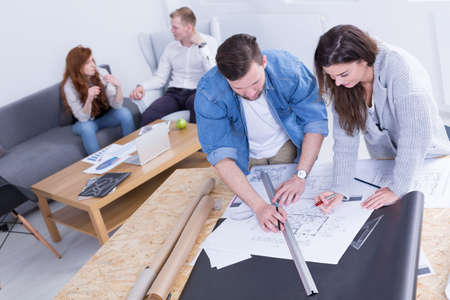 busy: Two co-workers are working on a project situated on drawing board while the others are discussing on something Stock Photo