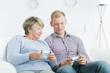Elderly woman and young man sitting on a sofa, holding gamepads